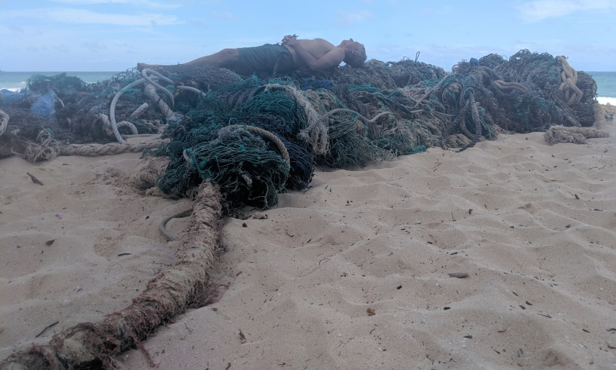 Bob Lyness on a pile of found rope garbage hauled from the sea, July 4, 2018 in Honolulu, Hawaii